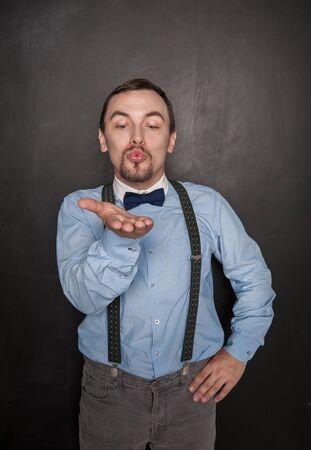 Handsome romantic man sending kiss on blackboard background Zdjęcie Seryjne