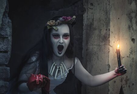 Creepy dead bride in white dress with candle screaming. Halloween scene