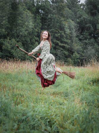 Piękna kobieta w średniowiecznej sukience latająca na miotle na zewnątrz Zdjęcie Seryjne