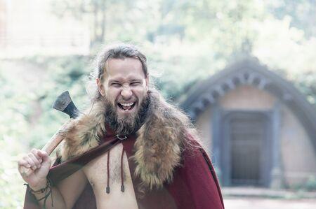 Guerrero vikingo hombre con hacha de hierro gritando al aire libre