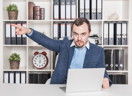 Angry boss business man pointing out in office