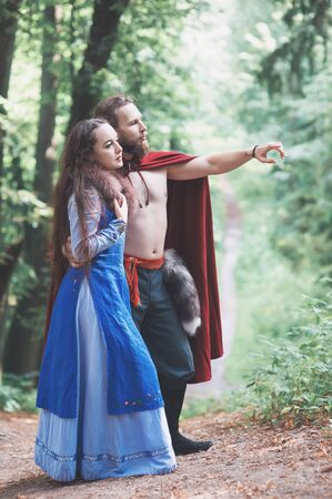 Handsome Warrior Viking man with beautiful medieval woman standing outdoor