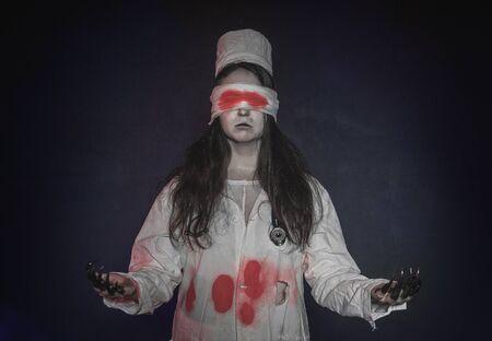 Terrible nurse woman with bloody bandage on her eyes. Halloween horror scene