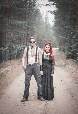 Terrible steampunk man and beautiful witch in forest