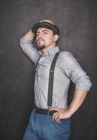 Handsome young man in retro style with cap on blackboard background