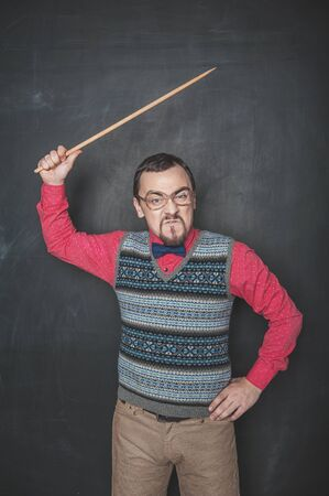 Angry business man or teacher with pointer on blackboard chalkboard background