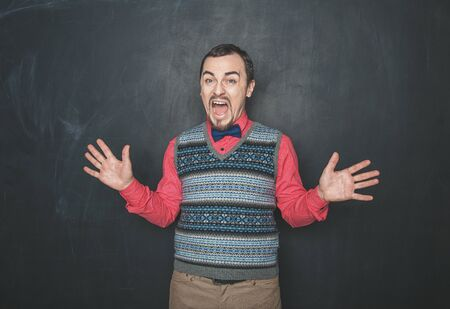 Funny Angry screaming teacher or business man on blackboard background