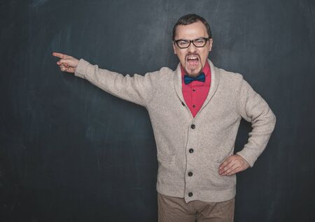 Angry teacher pointing out on blackboard chalkboard background