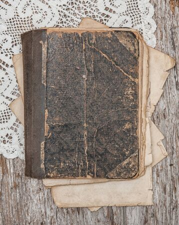 Old retro book cover with lace on the weathered vintage rustic wooden board