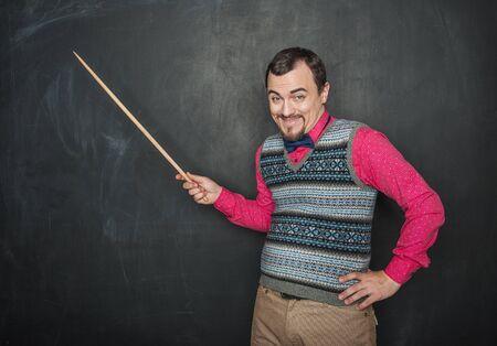 Lustiger kichernder Lehrermann mit Zeiger auf Tafelhintergrund Standard-Bild