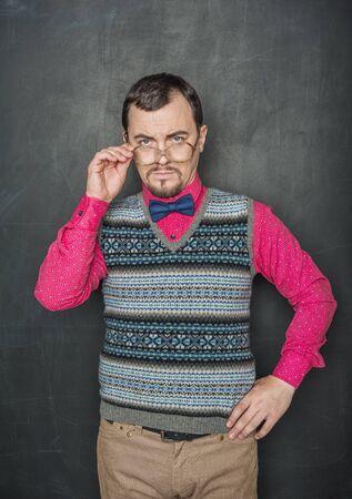 Strict teacher vintage style in eyeglasses looking at you on blackboard background