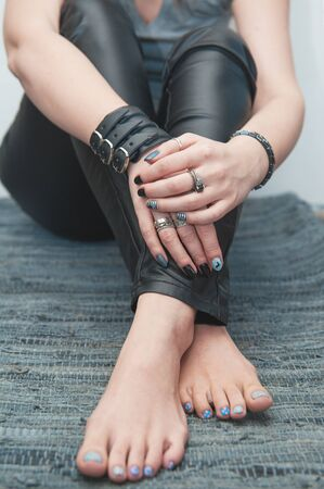 Fashionable trendy hipster woman with hands on barefoot legs Reklamní fotografie
