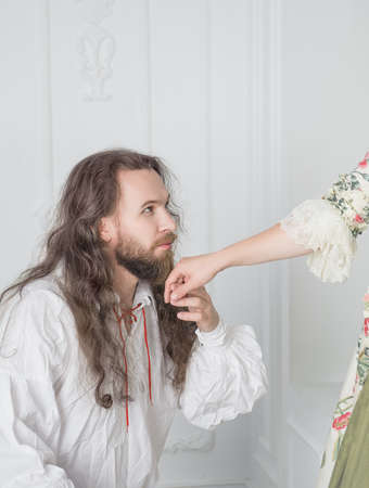 Handsome man in medieval dress kissing hand of beautiful woman Stock Photo
