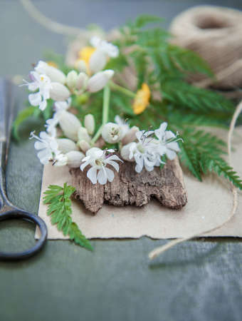 Old tailor scissors, rope and flowers on the wooden