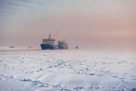 Winter shipping. Big cargo ship in frozen ice sea fairway