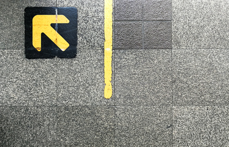 Granite floor with yellow arrow on top of black pad at queuing line in BTS skytrain station. Stock Photo