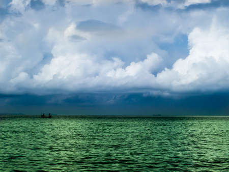 light complexion: Fishing boat and green sea on horizon line on blue sea