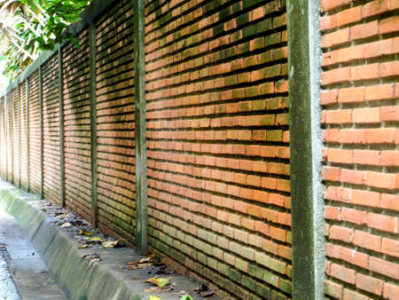 ancient brick wall: ancient brick wall has erosion and damage by wind and water beside way after rain fall