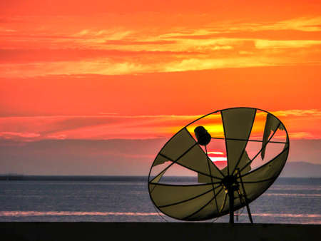 dish disk: satellite disk break and sunsets on horizonental line at the sea Stock Photo