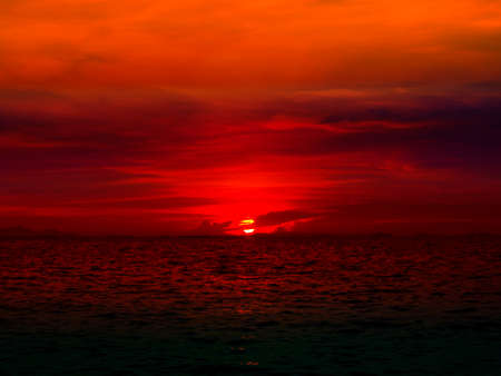 sunset last light of sun on horizontal line over red sky and red ocean