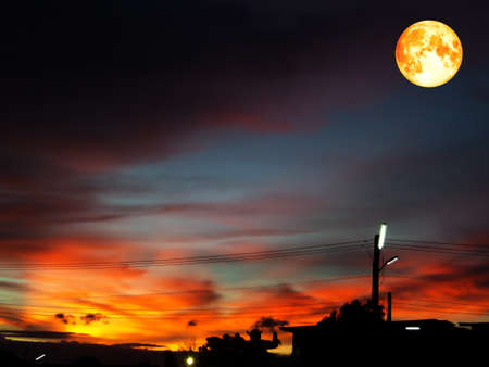 full blood moon on colorful sky in orange and dark gray cloud silhouette building