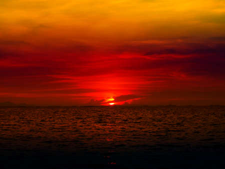 sunset last light of sun on horizontal line over orange sky and red ocean