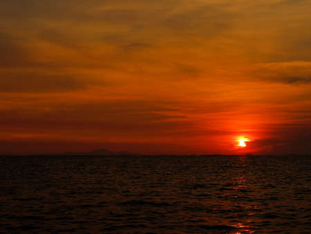 sunset last on horizontal in right frame over orange night sky and ocean Stock Photo