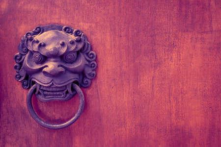 metal evil face pull door and hard wood surface background, concept : Dont open danger gate Stock Photo