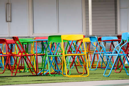 Multi-color steel chair set on green plastic grass In the public playground
