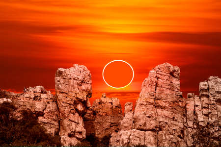 annular eclipse over stone on rock of cliff