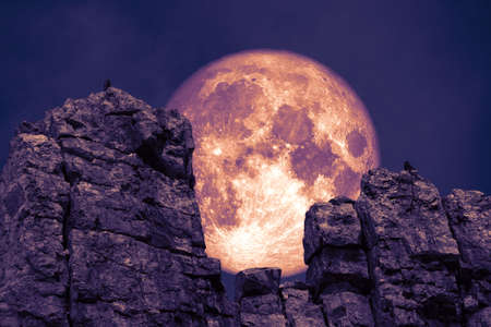 dark purple moon back over stone and monsters on rock between cliff
