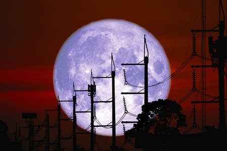Full Sprouting Grass Moon back on silhouette power electric line and pole on night sky, Elements of this image furnished by Archivio Fotografico