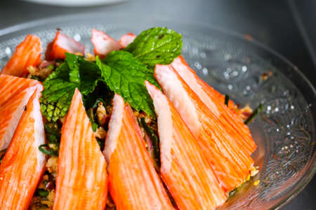 spicy minced crab sticks salad and mint leaves on top and glass dish