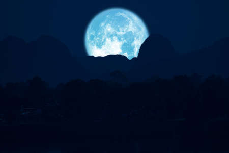 rose moon on night sky back over silhouette mountain Stock Photo