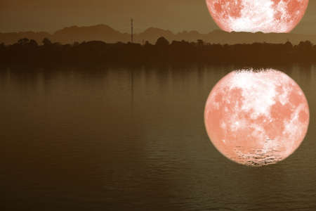 reflection on river of strawberry moon on night sky back silhouette mountain