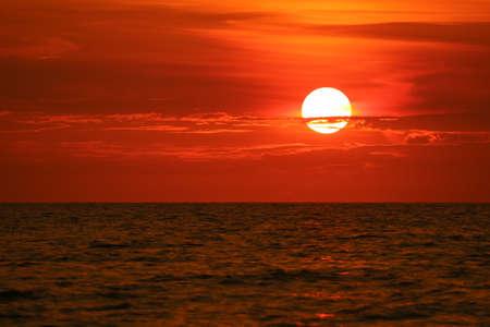 zon terug op de horizon van de zonsonderganghemel en golf op de oppervlaktezee