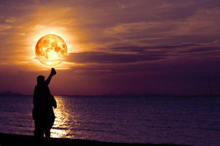 Amant de couple se réveillant ensemble sur la plage et selfie avec plein d'esturgeon sur la mer et reflet au clair de lune sur la surface de l'eau