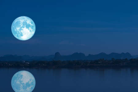 full milk moon back on silhouette mountain and reflection on river night sky