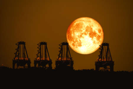 super harvest moon on night sky back  over silhouette cranes in seaport