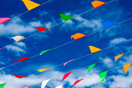 colorful triangular flag line moving by wind on blue sky white cloud background