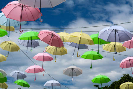 colorful umbrella line wire moving by wind on blue sky white cloud background