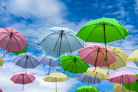 colorful fancy umbrella line decorate outdoor moving by wind on blue sky white cloud background Imagens