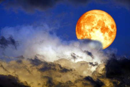 Luna de sangre de cosecha completa en la silueta de la nube en el cielo del atardecer