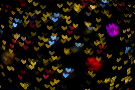 colorful abstract bokeh and blur heart shape love valentine night light on wall at shopping mall Imagens