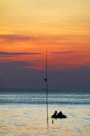 colorful rainbow of sunset on silhouette cloud sky and men on fishing boat on the sea