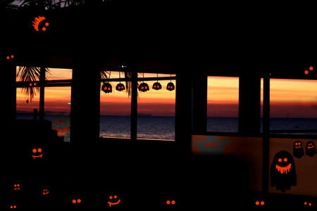 Old abandoned haunt house near the sea and ghosts spirits and tomb in Halloween day and sunset sky Stock fotó