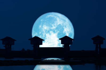 reflection Super blue moon and silhouette dam in the dark night sky 版權商用圖片
