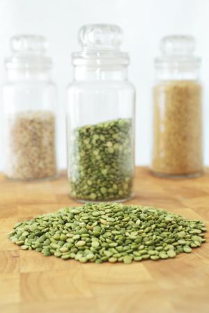 木の板、分割エンドウ豆の瓶とバック グラウンドで穀物の 2 つの jar ファイルに分割グリンピース 写真素材