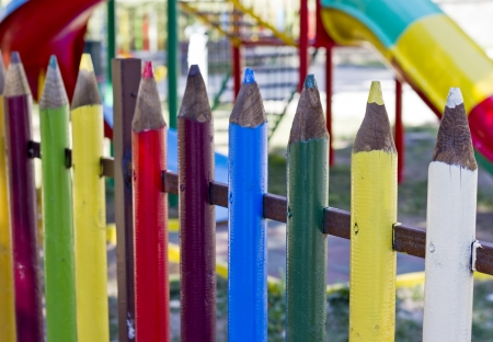 Colorful fence made of crayon-shaped pillars with childrens playground in the background Stock Photo