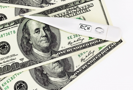 Money concept: thermometer on top of dollars showing rich instead of temperature Stock Photo
